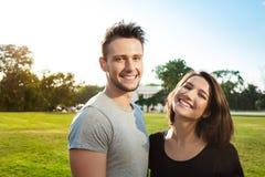 微笑年轻美好的夫妇画象,放松在公园 免版税库存图片