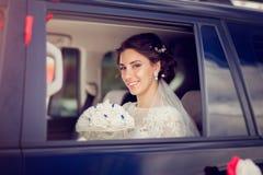 微笑从车窗的美丽的新娘 免版税库存图片