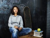 微笑年轻逗人喜爱的十几岁的女孩在黑板就座的教室在桌上,现代行家概念,生活方式人 图库摄影