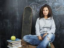 微笑年轻逗人喜爱的十几岁的女孩在黑板就座的教室在桌上,现代行家概念 库存图片