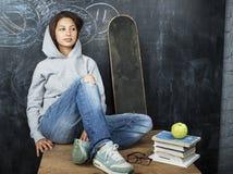 微笑年轻逗人喜爱的十几岁的女孩在黑板就座的教室在桌上,生活方式人概念 免版税库存照片
