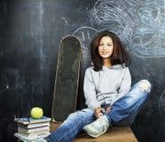 微笑年轻逗人喜爱的十几岁的女孩在黑板就座的教室在桌上,生活方式人概念 库存照片
