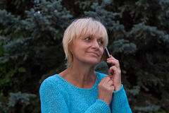 微笑ellderly妇女有一次交谈由电话 库存图片