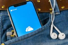 微软办公系统OneDrive在苹果计算机iPhone x屏幕特写镜头的应用象在牛仔裤装在口袋里 一个Drivet app象 微软Onedr 免版税库存照片