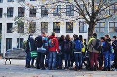 德国人和外国人旅客在看某事附近拥挤在庭院里 图库摄影