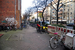 德国人民停止并且锁自行车在路旁边的自行车停车处 库存图片