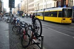 德国人民骑自行车的自行车和锁骑自行车在路旁边的自行车停车处为去乘客电车轨道网络 库存照片