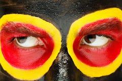 德国体育迷爱国者 在恼怒的人面孔的被绘的国旗 恶魔眼睛关闭  免版税库存照片