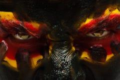 德国体育迷爱国者 在恼怒的人面孔的被绘的国旗 恶魔眼睛关闭  免版税库存图片