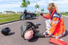 德国医务人员帮助一名受伤的摩托车骑士 库存图片