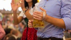德国啤酒大啤酒杯和传统衣裳 免版税库存图片