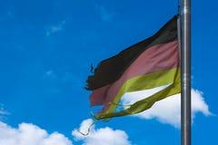 德国在蓝天Backgrou的旗子黑色红色金子爱国标志 免版税图库摄影