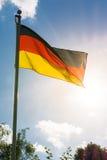 德国在蓝天Backgrou的旗子黑色红色金子爱国标志 免版税库存图片