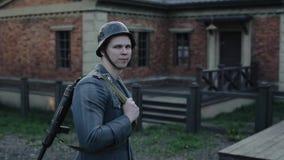 德国士兵的背面图有一杆步枪的在审阅篱芭的门的他的,敲在红色的门 股票视频