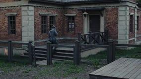 德国士兵的背面图有一杆步枪的在审阅篱芭的门的他的,敲在红色的门 股票录像