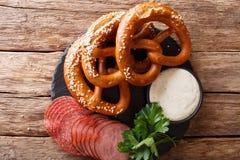 德国开胃菜:切的蒜味咸腊肠和椒盐脆饼与调味汁特写镜头 库存图片