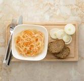 德国泡菜用葱和面包在一个木板 库存照片