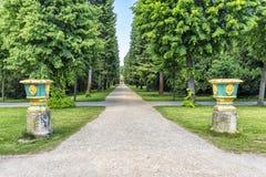 德国波茨坦公园Sanssouci 在树之间的宫殿庭院里铺石渣道路往陵墓 免版税库存图片
