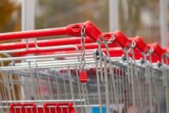 德国超市连锁, Rewe的购物车在停车场连续一起站立 免版税图库摄影