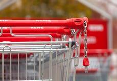 德国超市连锁, Rewe的购物车在停车场连续一起站立 免版税库存图片