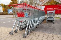 德国超市连锁, Rewe的购物车在停车场连续一起站立 库存图片