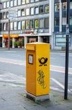 德国邮政敦豪航空货运公司-邮箱在城市 免版税库存图片