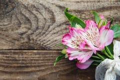 德国锥脚形酒杯桃红色花花束在木背景的 图库摄影