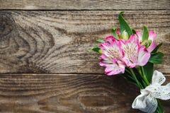 德国锥脚形酒杯桃红色花花束在木背景的 免版税库存图片