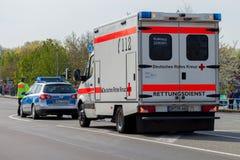 德国紧急救护车和警车在街道上站立 免版税图库摄影