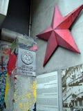 德意志民主共和国标志和红色星,专栏和柏林墙在东部和西部区段之间的检查站查理附近分配 库存照片
