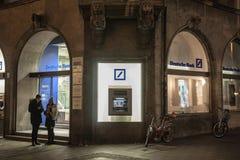 德意志银行商标和ATM在多雪的夜期间被采取的他们的一个慕尼黑分支 库存图片
