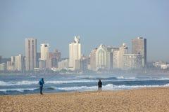 德班海滩的两位渔夫与旅馆在背景中 免版税库存照片