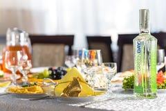 德罗霍贝奇,乌克兰- 2017年8月12日:年轻岁月在欢乐桌上的瓶伏特加酒,婚姻的桌在餐馆 库存图片