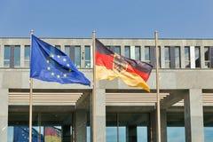 德语和挥动反对现代办公楼的欧盟旗子 库存图片