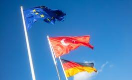 德语,欧盟,在白色杆的土耳其挥动的旗子 背景蓝天 免版税库存图片