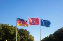 德语,欧盟,在白色杆的土耳其挥动的旗子 自然和天空蔚蓝背景 库存照片