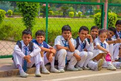 德里,印度- 2017年9月16日:佩带体育的未认出的小组孩子在穿衣,坐在户外 库存照片