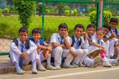 德里,印度- 2017年9月16日:佩带体育的未认出的小组孩子在穿衣,坐在户外 免版税库存照片