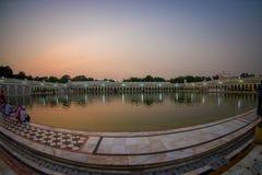 德里,印度- 2017年9月19日:在著名锡克教徒的gurdwara金黄寺庙Harmandir Sahib的美好的日落反射了  图库摄影
