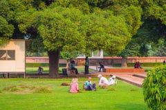 德里,印度- 2017年9月25日:坐在公园的未认出的人民在室外在德里红堡在德里, a的 免版税库存照片