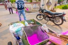 德里,印度- 2017年9月19日:有桃红色尘土的未认出的人驱散在街道的,准备区域 免版税库存图片