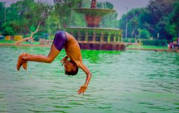 德里,印度- 2017年9月16日:未认出的印地安男孩在水中的做一backflip,绿色水在一个池塘在德里 免版税图库摄影