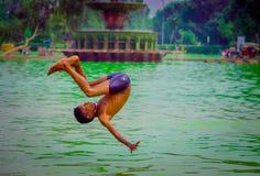 德里,印度- 2017年9月16日:未认出的印地安男孩在水中的做一backflip,绿色水在一个池塘在德里 免版税库存照片