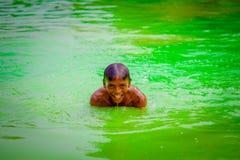 德里,印度- 2017年9月16日:未认出的印地安男孩游泳和使用在水,绿色水中在池塘  库存图片