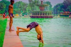 德里,印度- 2017年9月16日:未认出的印地安男孩跳跃到水的,绿色水在一个池塘在德里,印度 库存图片