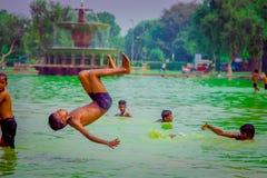 德里,印度- 2017年9月16日:未认出的小组印地安男孩smming和做在的一个唯一男孩一backflip 图库摄影