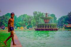 德里,印度- 2017年9月16日:未认出的愉快的印地安男孩站立在池塘的边界的,在a的绿色水 图库摄影