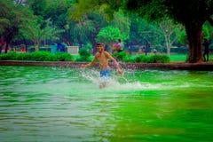 德里,印度- 2017年9月16日:未认出的愉快的印地安男孩跑在池塘的,绿色水在德里 库存图片