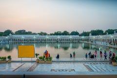 德里,印度- 2017年9月19日:游泳和洗涤他们的头的未认出的人民如幸运在的池塘 免版税库存图片