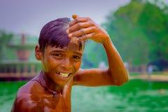 德里,印度- 2017年9月16日:画象未认出的微笑的印地安男孩,接触他的头用他的手 库存照片
